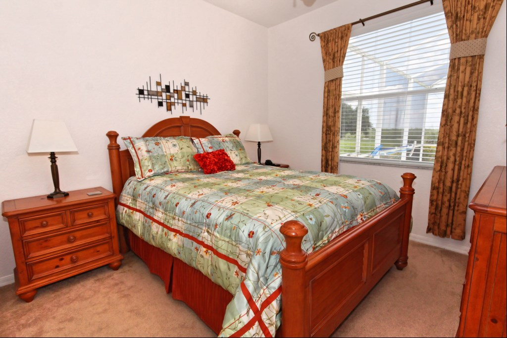 Bedroom 2 with ensuite bathroom, queen-sized bed and views over pool deck