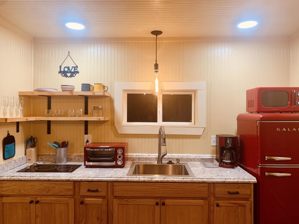 Functional kitchen offers a microwave, 2-burner stove and toaster oven.