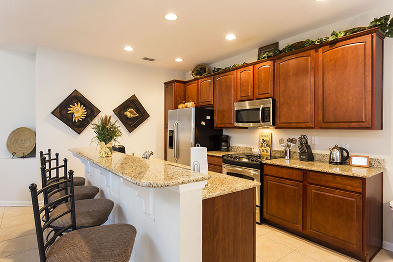 Beautiful kitchen area with microwave, oven, double door refrigerator and barstool seating