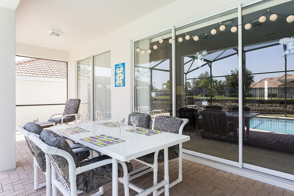 View 2 of luxurious patio furniture with pool, spa, and sliding glass door to access the villa