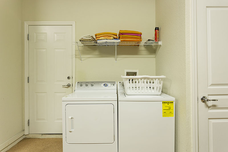 Laundry room with full size washer and dryer inlcuding laundry basket and towels