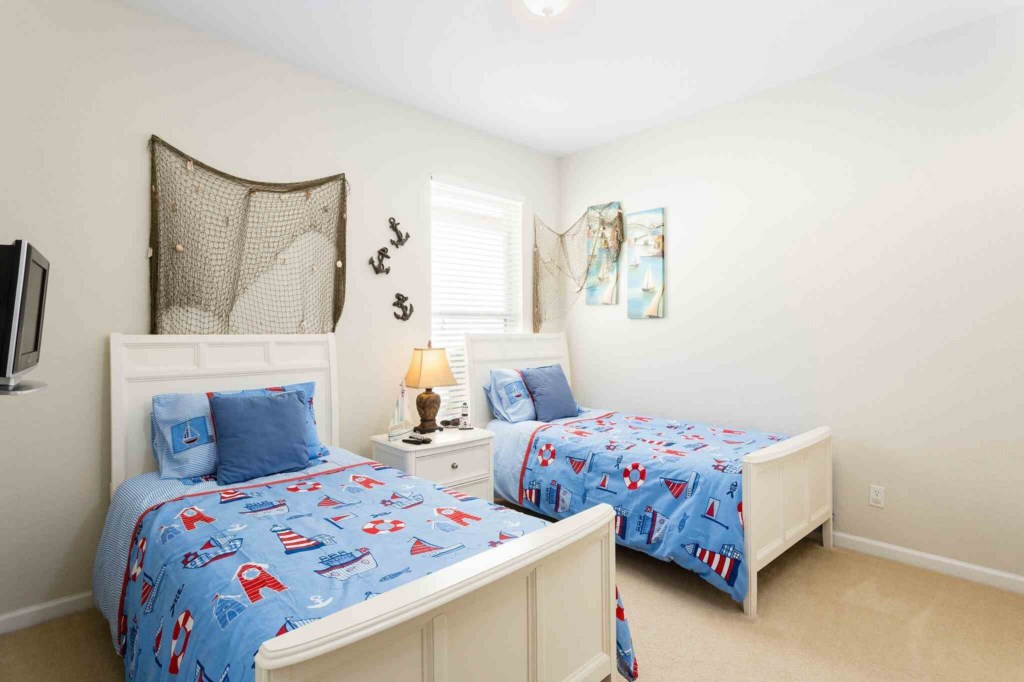 Two adorable nautical themed twin beds with flat screen TV