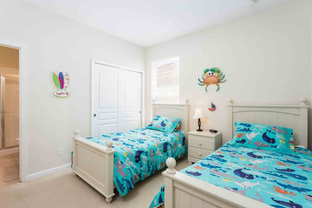 Two fun ocean themed twin beds with flat screen TV
