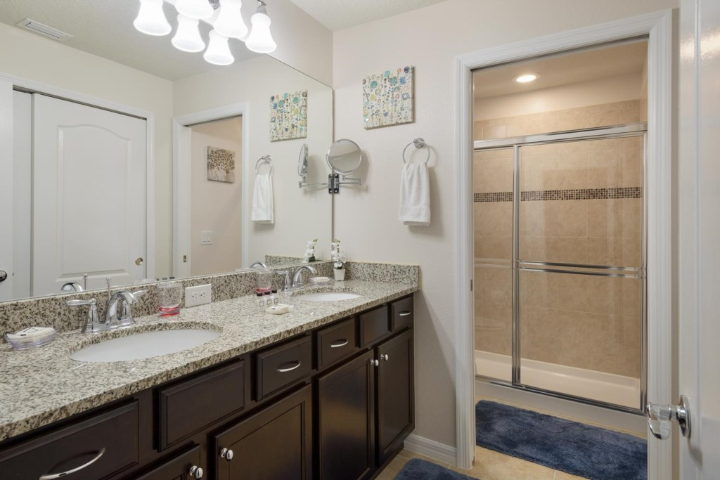 Upstairs suite 1 private bathroom has a glass door shower and vanity with two sinks