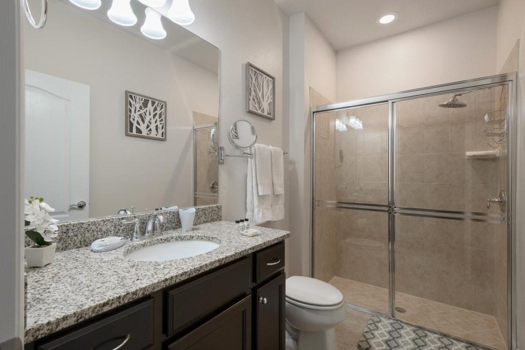 Downstairs bathroom 3 has a glass door shower with a rain showerhead