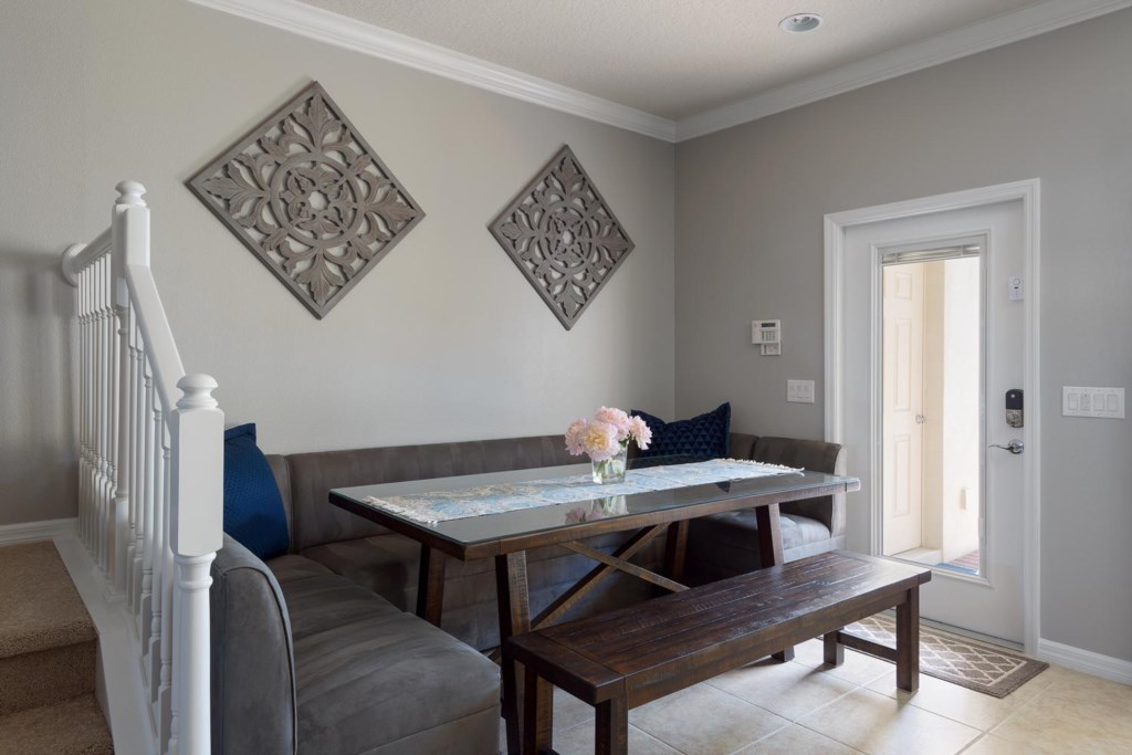 The dining area features upholstered booth-style and bench seating for eight