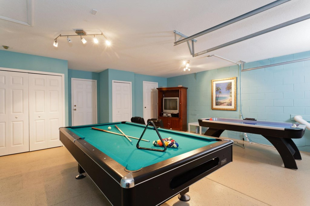 Spacious game room includes pool and air hockey tables plus a 32-inch TV and PS2