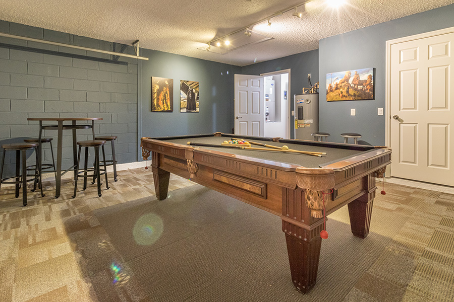 Game room with pool table and bar stool seating