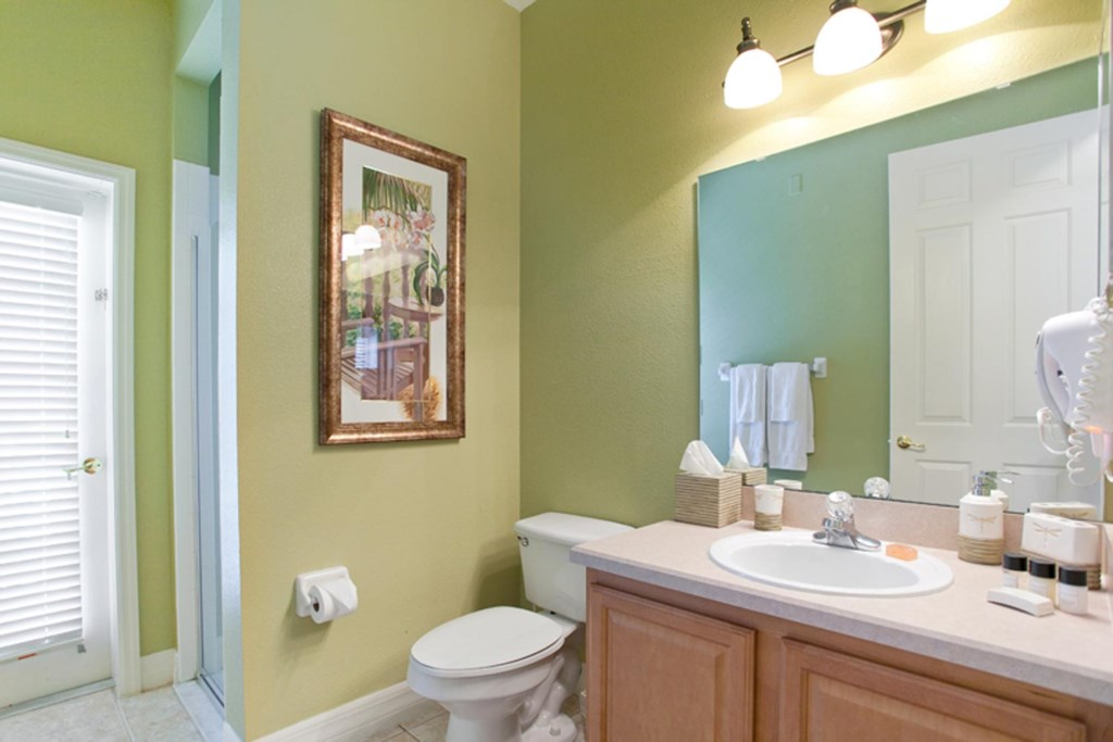 Downstairs hall bathroom 5 with glass door shower and access to the lanai and pool area