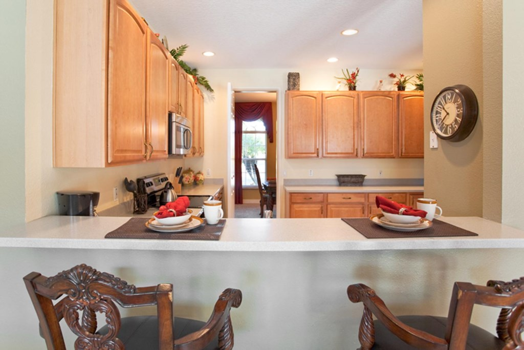 The kitchen includes a dining counter with seating for two