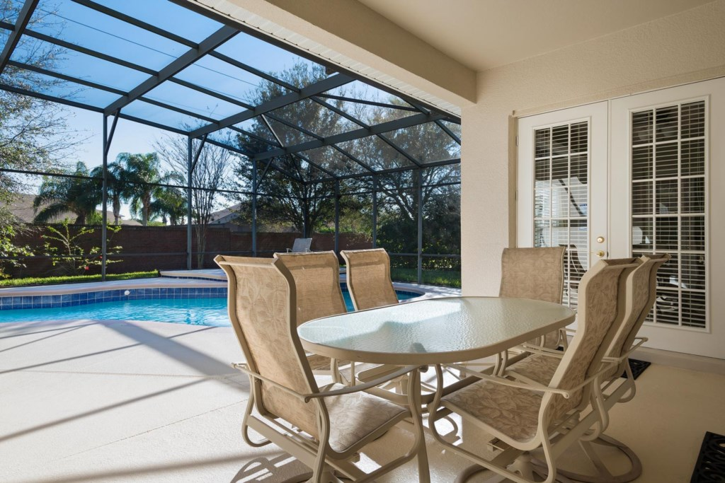 The covered lanai features a casual outdoor dining area