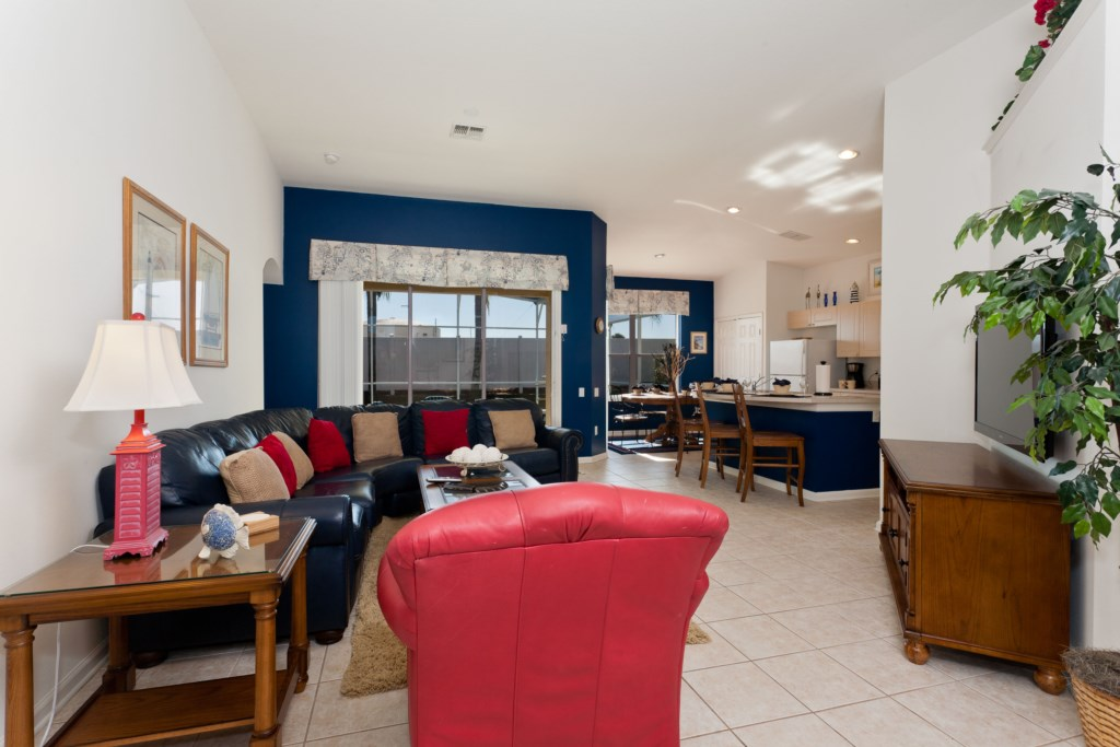 The living area is spacious and features direct pool/patio access