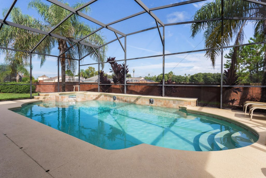 Splash and play the day away in the screened-in north facing private pool with a spillover spa