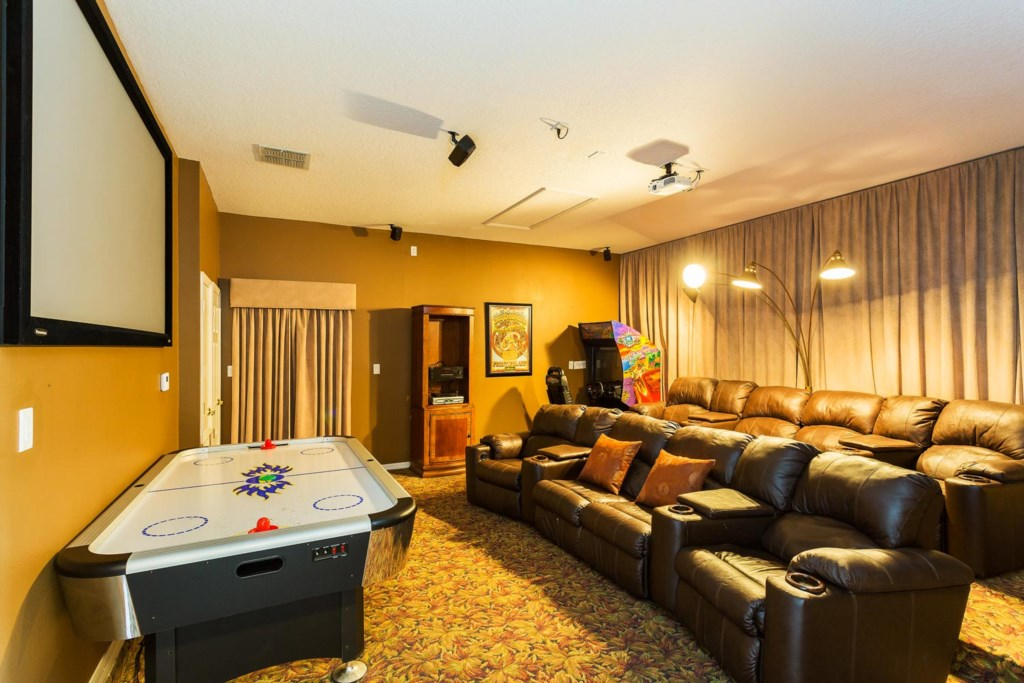 Home theater/game room with two arcade machines, air hockey, tiered seating, 92-inch projection scre