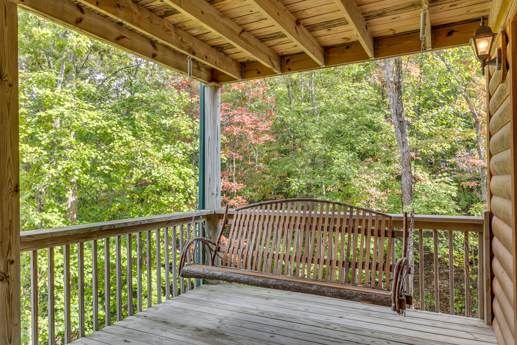 Traditional porch swing on Treetops back porch offers a great vantage point for those beautiful view