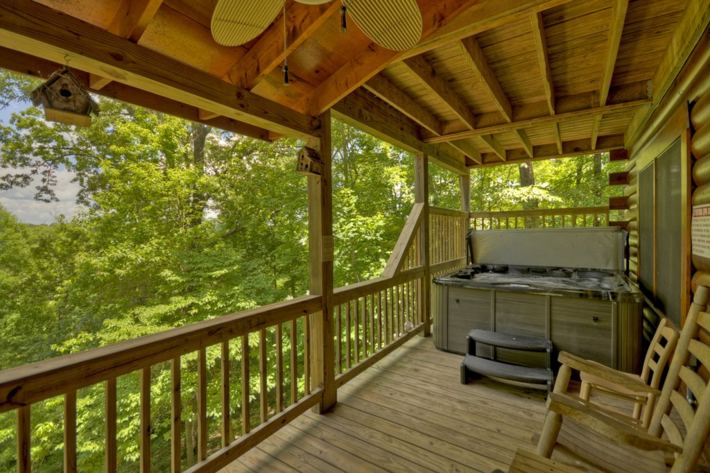 Covered hot tub & seating overlook the view from Bear Ridge`s porch