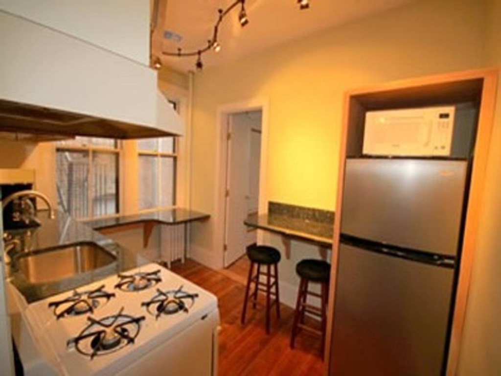Granite-countered kitchen with small stove/oven, dishwasher and full size fridge