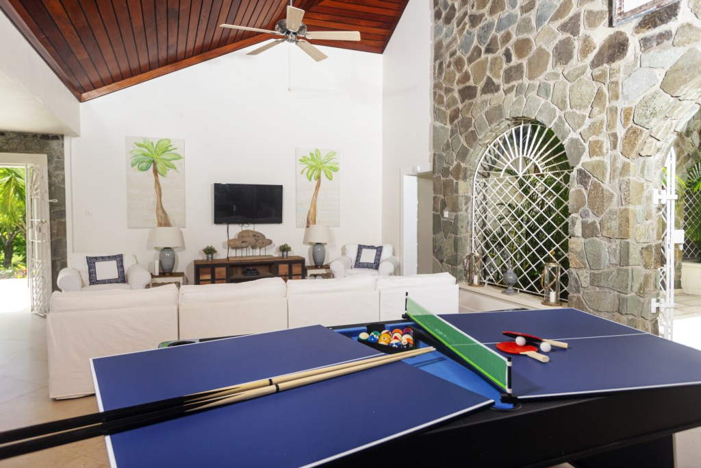 Billiards table located inside and a table tennis set up outside.