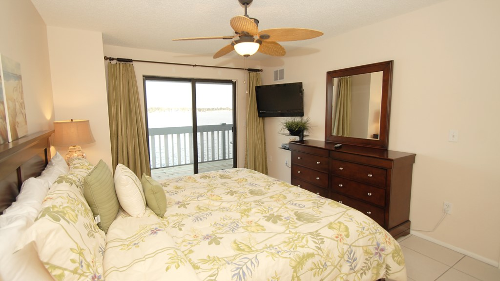 Master bedroom, flat screen television and balcony overlooking the water