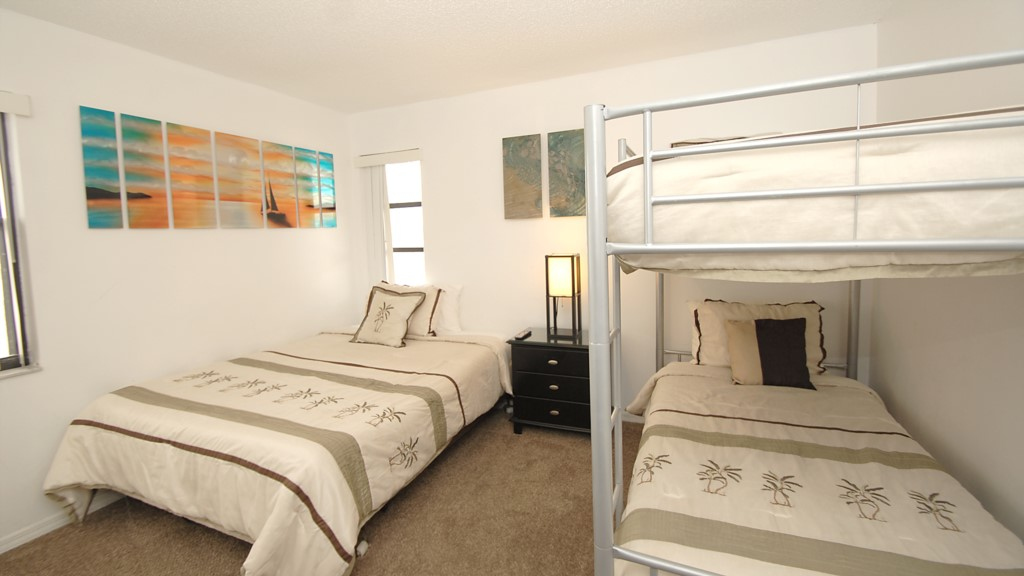 Secone bedroom with a queen bed and bunk beds