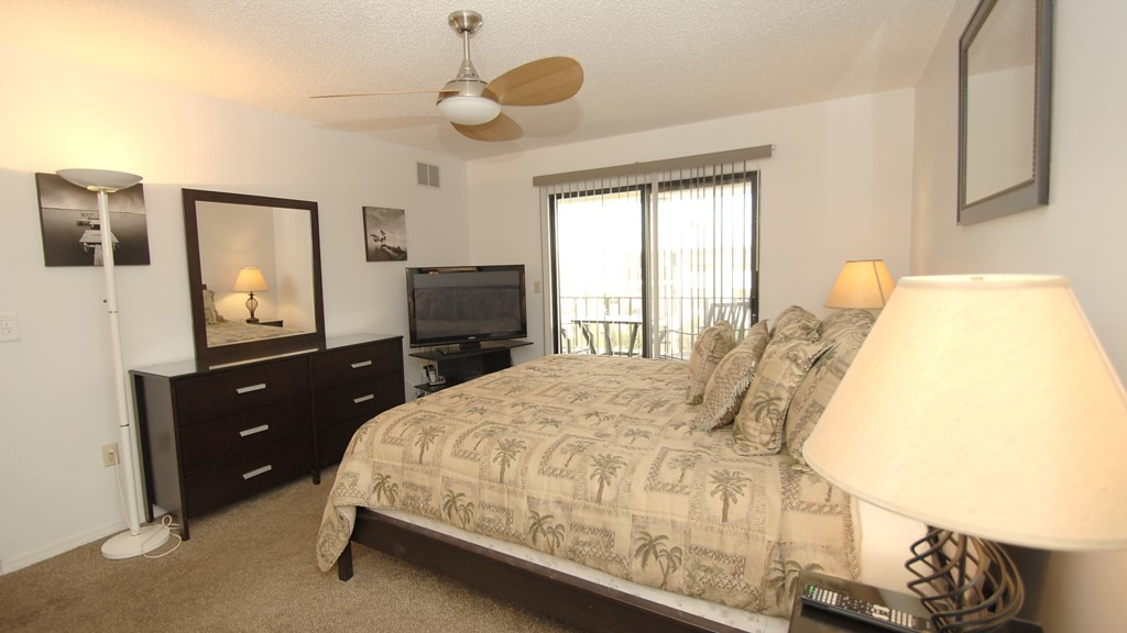 Master bedroom and the sliding glass doors lead out onto the west balcony overlooking the pool and a