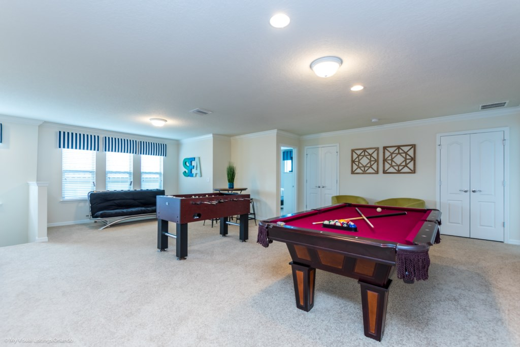 View 2 of fun entertainment room including pool table, foosball, lounge area and flat screen TV