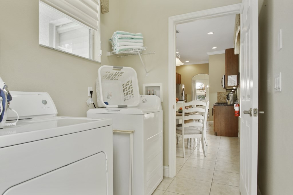 Laundry Room off the kitchen with door leading to the pool area. Full size washer & dryer.
