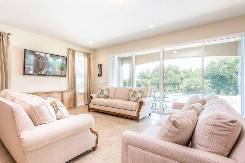 Open concept living room with seating for 9, overlooking swimming pool.