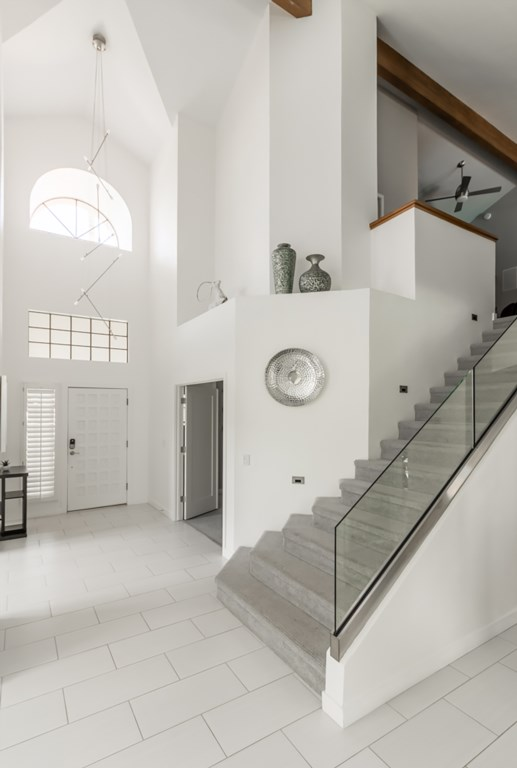 Beautiful entry way with modern staircase leading to the movie room