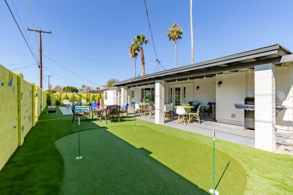 Private backyard with pool, lounge chairs, putting green, fire pit, Grill, TV and yard games