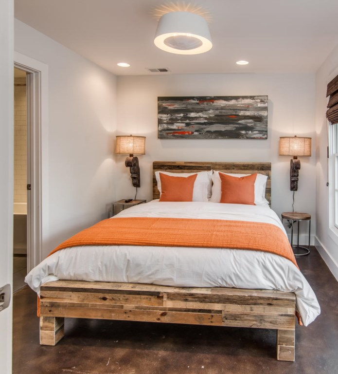 The 2nd bedroom is outfitted with a queen bed, warm colors, and eye-catching wood details.