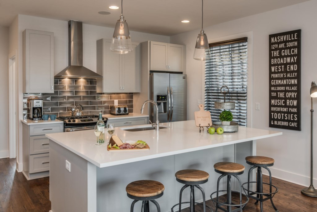 The stunning kitchen has a center island with 4 seats, a gas range, and a side-by-side fridge.