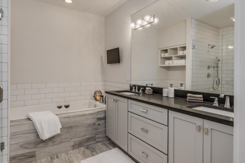 The richly detailed master bath has a double vanity and soaking tub with a flat screen TV.