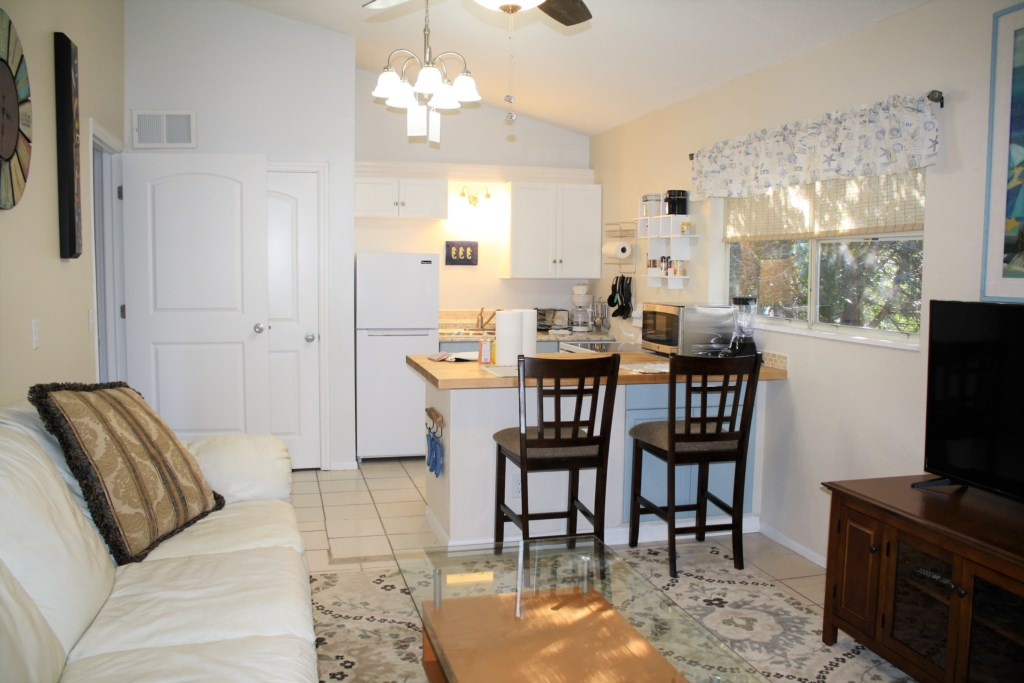 Bright and airy kitchen/living room with new appliances.