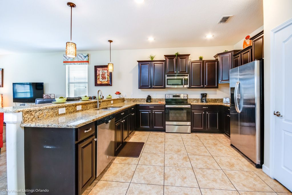 Classy kitchen area with refrigerator, pantry, and flat screen TV