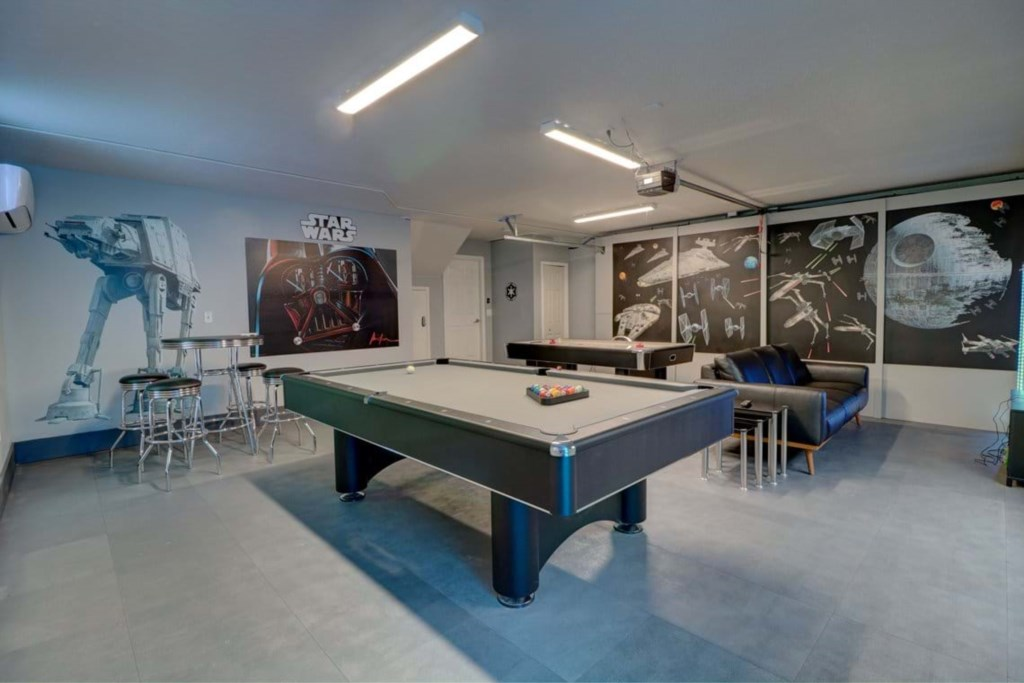 Exciting Star Wars game room with air hockey, pool table, and lounge area with flat screen TV and AC