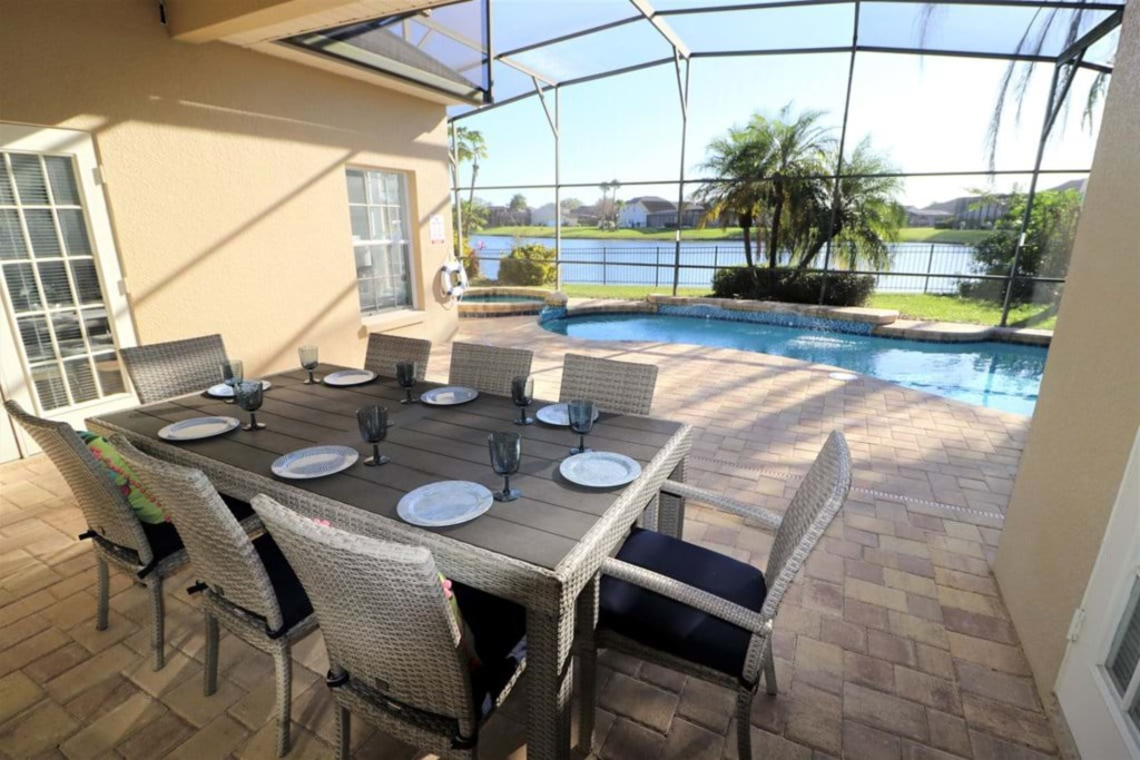Grand patio area with table seating eight with view of the pool and spa
