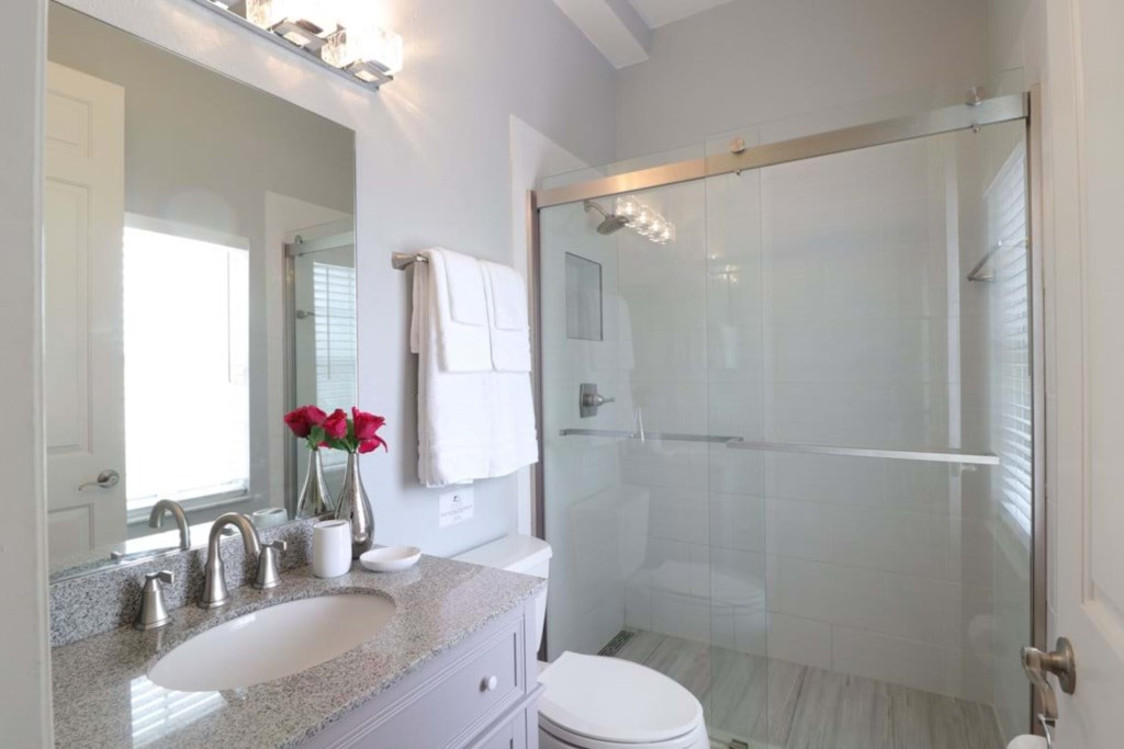Modern style bathroom with single sink vanity, sliding glass shower, and toilet