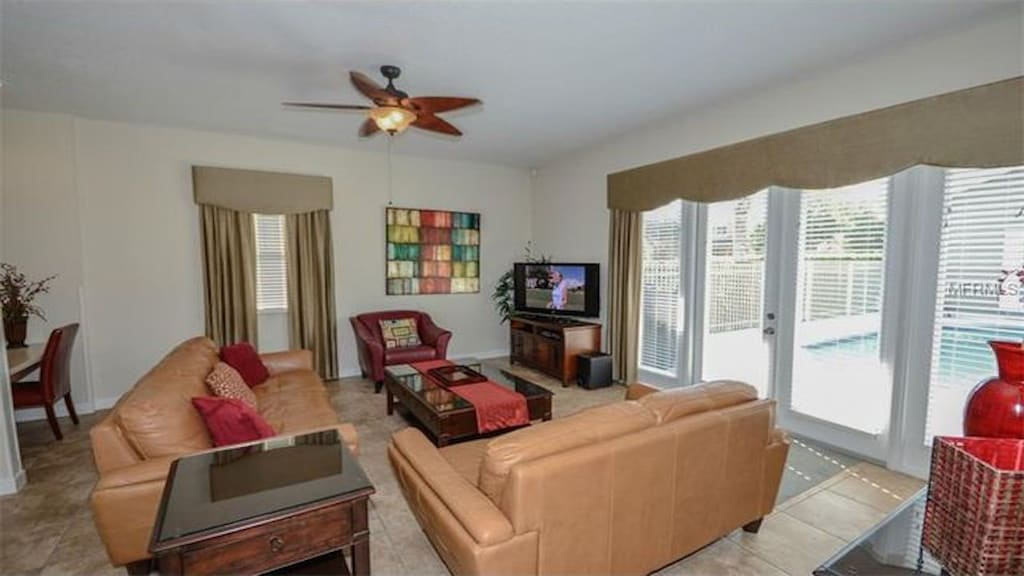 Family room overlooking the pool area. TILED WITH LEATHER SOFAS