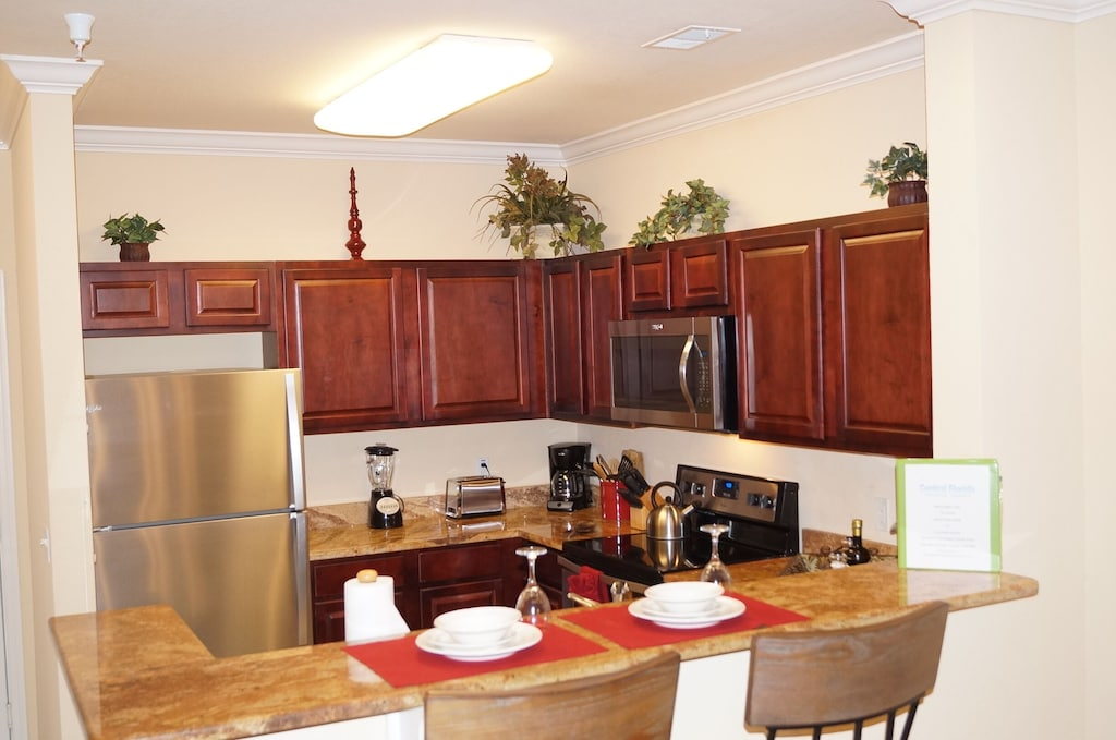Kitchen with full size refrigerator, stainless appliances and cooking amenities