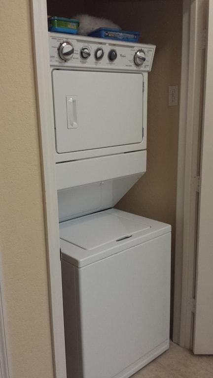 Washer and dryer combo usually hidden behind door in condo laundry closet.