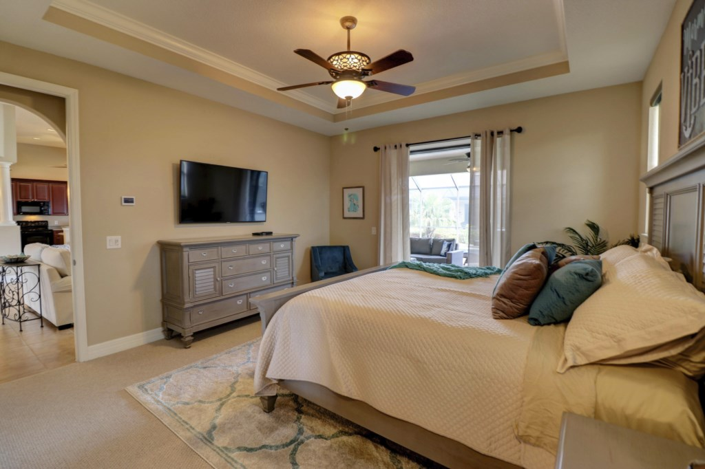 Cozy Master Suite with ceiling fan and large TV