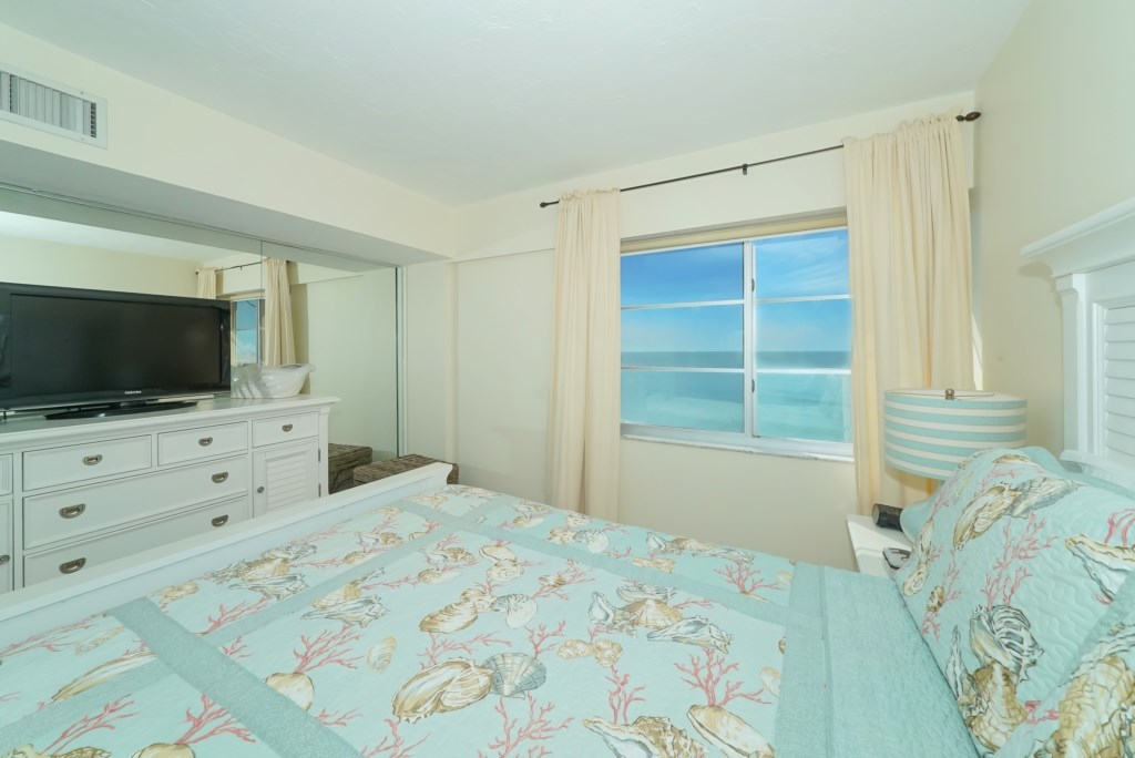 Bedroom with tv and window towards the ocean