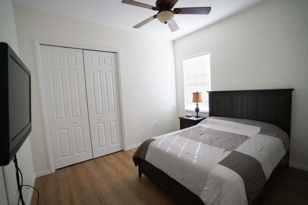 Guest bedroom with closet and queen bed