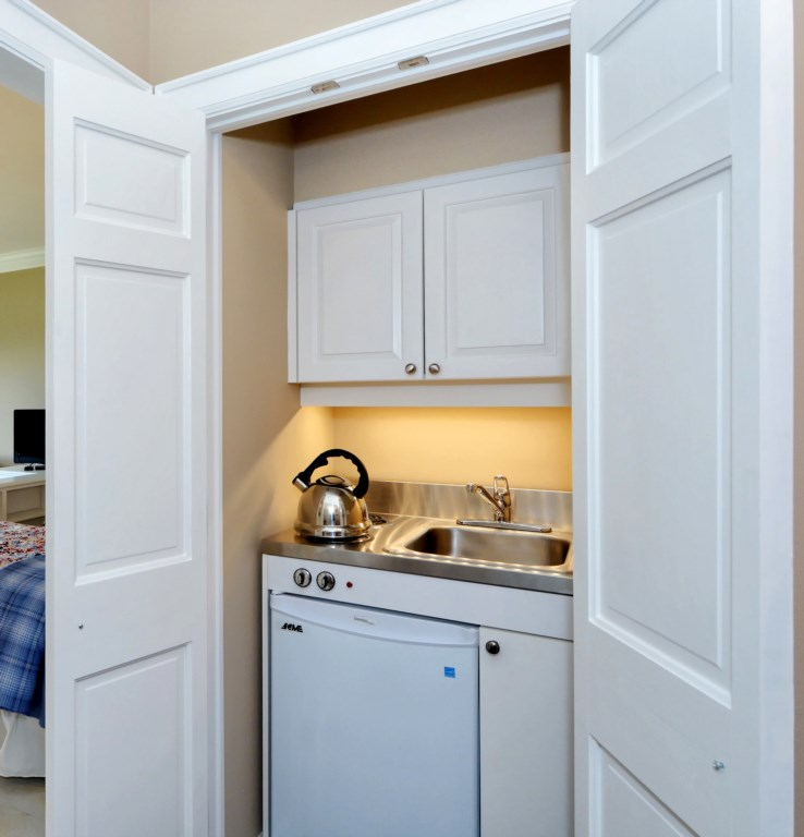 Kitchenette with stove, sink and fridge