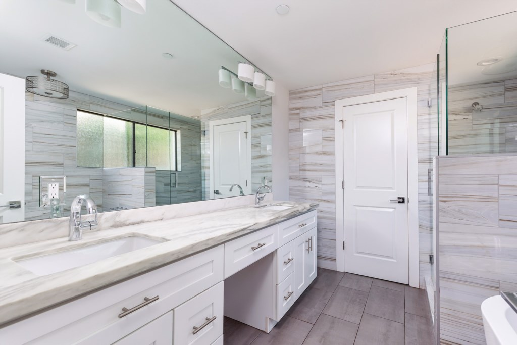 Master bathroom with double sink vanity, large seamless shower door and floating tub
