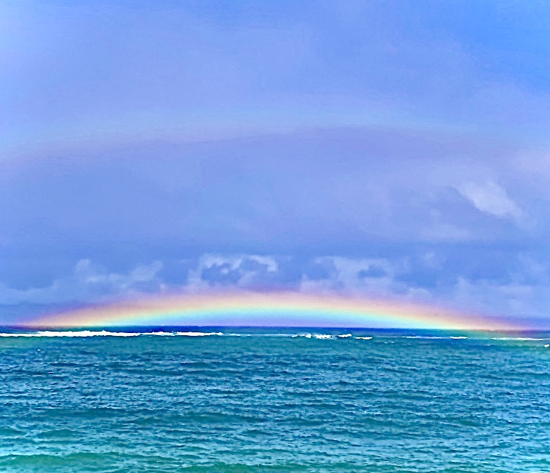The magnificant colors of the rainbow reflecting on the Ocean.