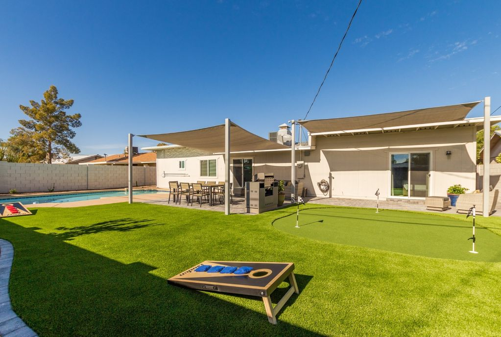 Large backyard with yard games and putting green