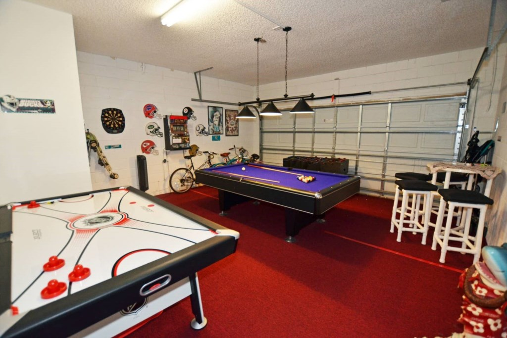 Game room with air hockey,pool,foosball table, bar stool, bicycles, and strollers.jpg