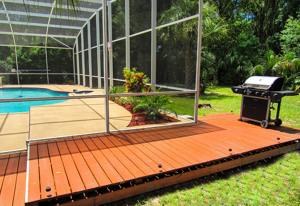 Decking area outside pool screen, with gas grill included.